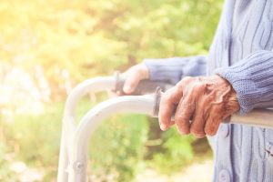 Senior woman to use walking frame in a sunny park