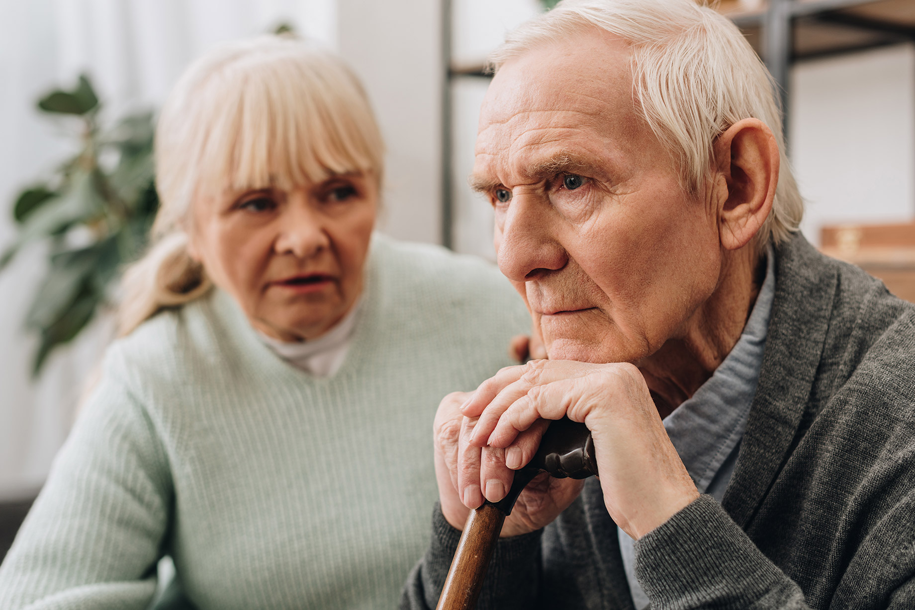 sad pensioner sitting near senior wife at home