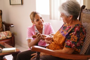 A nurse helps the senior woman