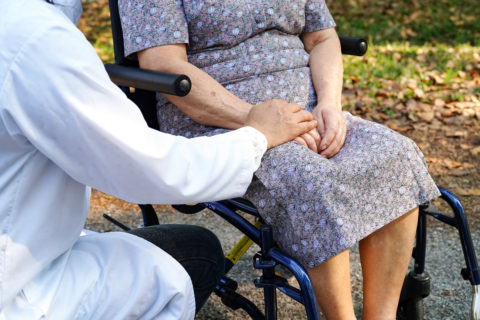 Doctor holding the hand of an elderly lady sitting in a wheelchair