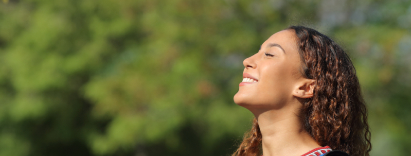 Happy young lady breathing in deeply the fresh air whilst standing in a park