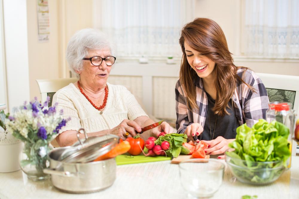 Grandmother and granddaughter preparing food