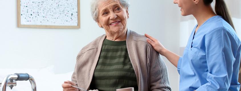 Care worker serving dinner for elderly woman